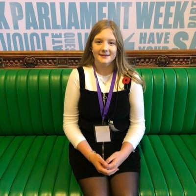 Ellie Craig MSYP sits on a green bench at Parliament